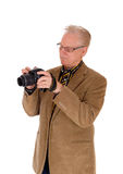 Middle age man taking pictures. A mature man in a brown jacket holding a camera and taking pictures Stock Images