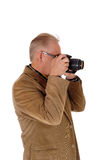 Middle age man taking pictures. A older man in a brown jacket holding a camera and taking pictures Royalty Free Stock Images
