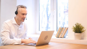 Middle Age Man Talking in Call Center, Customer Service. High quality royalty free stock photo