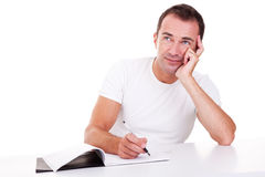 Middle-age man thinking and writing, looking up Royalty Free Stock Image