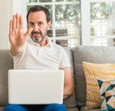 Handsome senior man at home. Middle age man using laptop at sofa with open hand doing stop sign with serious and confident expression, defense gesture stock images