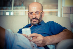 Middle age man using phone. At home Royalty Free Stock Photography