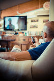 Middle age man watching tv. At home Royalty Free Stock Image