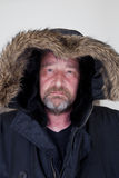 Middle Age Man Wearing Fur Lined Hooded Shirt. Close up Middle Age Man with Beard and Mustache Wearing Black Fur Lined Hooded Shirt on a Gray Background, Looking Stock Photos