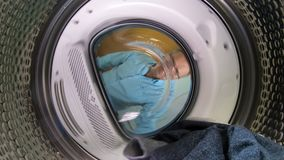 Man loading the the clothes to washing machine. Middle age man wearing glasses loading the the clothes to washing machine. View from the inside of washing stock footage
