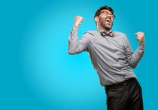 Middle age man wearing a suit. Middle age man, with beard and bow tie happy and excited celebrating victory expressing big success, power, energy and positive Royalty Free Stock Photo