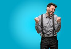 Middle age man wearing a suit. Middle age man, with beard and bow tie happy and excited expressing winning gesture. Successful and celebrating victory Royalty Free Stock Photos
