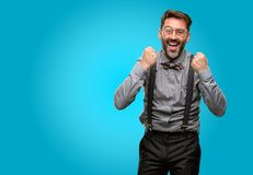 Middle age man wearing a suit. Middle age man, with beard and bow tie happy and excited expressing winning gesture. Successful and celebrating victory Stock Image