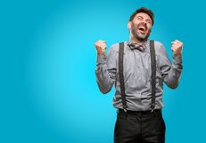 Middle age man wearing a suit. Middle age man, with beard and bow tie happy and excited expressing winning gesture. Successful and celebrating victory Royalty Free Stock Photography