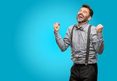 Middle age man wearing a suit. Middle age man, with beard and bow tie happy and excited expressing winning gesture. Successful and celebrating victory Stock Photo