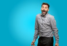 Middle age man wearing a suit. Middle age man, with beard and bow tie happy and surprised cheering expressing wow gesture stock photos