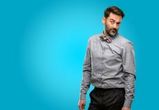 Middle age man wearing a suit. Middle age man, with beard and bow tie having skeptical and dissatisfied look expressing Distrust, skepticism and doubt royalty free stock images