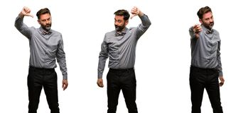 Middle age man wearing a suit. Middle age man, with beard and bow tie showing thumbs down unhappy sign of dislike, negative expression and disapproval Stock Photos