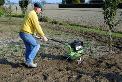 Middle Age Man With A Rototiller Royalty Free Stock Photos