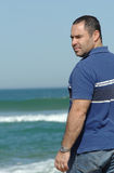 Middle age men looking the horizon. Middle age caucasion men looking the horizon near the water on the beach Stock Image