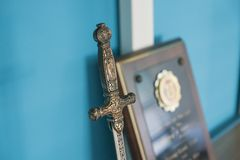 Middle age model sword and plaque on the wooden shelf stock photos
