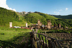 Middle Age mountain village with old huts and fence. Royalty Free Stock Photos