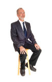 Middle age professional man sitting on a chair. Royalty Free Stock Photos