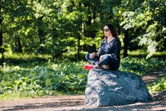 Middle age redhead caucasian woman sitting on a rock in lotus position stock photography