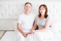 Middle age senior couple in bed. Template and blank t shirt. Front view. Healthy relationships. Copy space royalty free stock photos