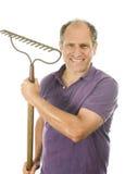 Middle age senior man holding garden bow rake tool Stock Image