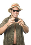 Middle age senior tourist male digital camera. Middle age senior tourist male wearing funny sun hat sunglasses and taking photo with digital camera Royalty Free Stock Image