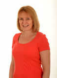 Middle age smiling woman. Portrait of a middle age, smiling woman wearing a bright orange blouse on a white background royalty free stock photos