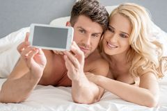 Middle Age Sweet Lovers Taking Photos on Bed Stock Photos