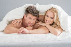 Middle Age Sweet Lovers on White Bed Royalty Free Stock Photos