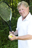 Middle age  tennis player demonstating stroke. Middle age senior handsome man tennis player demonstrating tennis stroke with racket and ball Royalty Free Stock Photos