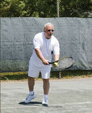 Middle age tennis player service motion on court. Handsome middle age male tennis player about to serve ball on tennis court at club Royalty Free Stock Photo