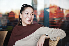 Middle age woman. Middle age mixed race woman sitting on the chair, laughing Stock Photo