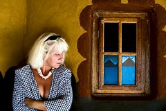 Middle age woman. Blonde middle age Caucasian woman ,spying on the window, traditional African house Royalty Free Stock Photos