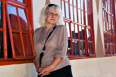 Middle age woman. Casual middle age woman against red windows. People diversity series Stock Image
