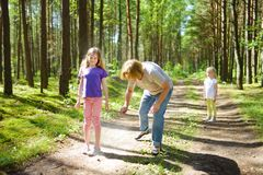 Middle age woman applying insect repellent to her granddaughter before forest hike beautiful summer day. Protecting children from stock photo