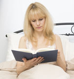 Middle Age Woman in Bed Reading Book Royalty Free Stock Photography