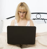 Middle Age Woman in Bed Using Laptop Royalty Free Stock Photos
