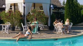 Middle age woman drinks a coffee and young woman sits by the pool while a group of teenagers is chatting at another table stock video