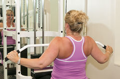 Middle age woman exercise. A middle age woman exercising or working out on a weightlifting machine Stock Photo