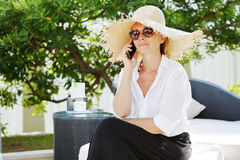 Middle age woman in garden. Portrait of middle age woman sitting at garden and making call while smiling royalty free stock photo