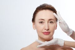 Middle age woman getting spa treatment. Face massage. Anti aging botox and collagen. Plastic surgery concept with doctor hands iso. Lated on white background stock photos