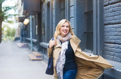 Middle age woman goes through the city and smiles. Happiness con. Cept Stock Image