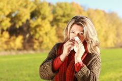 Middle age woman with handkerchief and cold outdoor. Blowing her nose Royalty Free Stock Photography