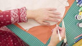 Middle-age woman hands drawing outline of a paper pattern with a pencil. Top view. Middle-age woman hands drawing outline of a paper pattern with a pencil on royalty free stock images