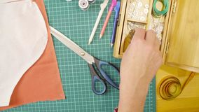 Middle-age woman hands pinning a paper pattern to the fabric with pins stock image