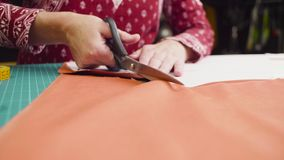 Middle-age woman hands with scissors cutting fabric royalty free stock photography