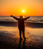 Middle age woman happy near sea sunset. In orange light Stock Images