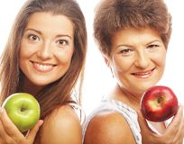 Middle age woman with her daughter holding apples. Middle age women with her daughter holding apples. Isolated on white Royalty Free Stock Photos
