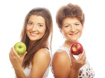 Middle age woman with her daughter holding apples. Middle age women with her daughter holding apples. Isolated on white Royalty Free Stock Photography