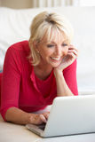 Middle age woman on her laptop computer. At home Royalty Free Stock Photo